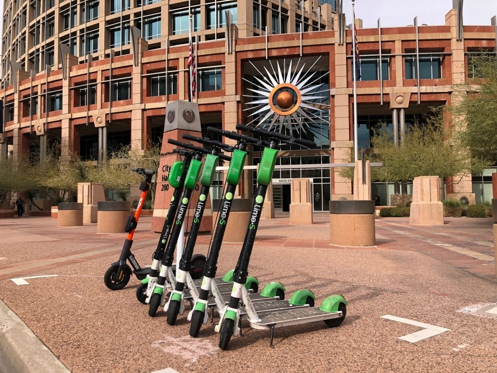 Lime and Spin scooters sit outside Phoenix city hall